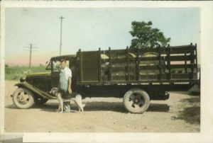 a postcard of a man standing in front of a truck filled with tubs of swiss cheese