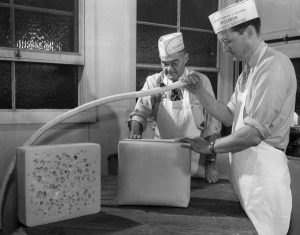 A black and white image of two men cutting Swiss cheese