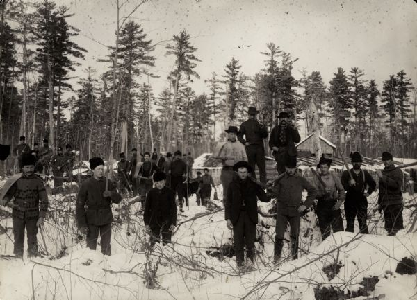 Men pose in the snow in a logging camp