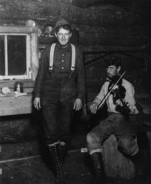 a fiddle player and jig dancer in a lumber camp