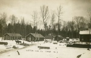 a black and white photo of a lumber camp showing several buildings in the snow