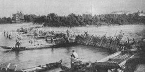 Men in boats fishing beside a wooden weir