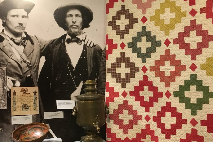 an image showing a colorful quilt and a black and white photo of two men with hats