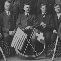 a group of dairymen pose with an american and a swiss flag