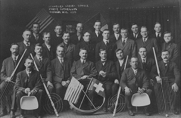 A group photo showing a gathering of men behind an American and a Swiss flag