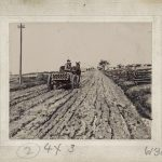 A man hauling pipes in a wagon over deeply rutted and muddy roads