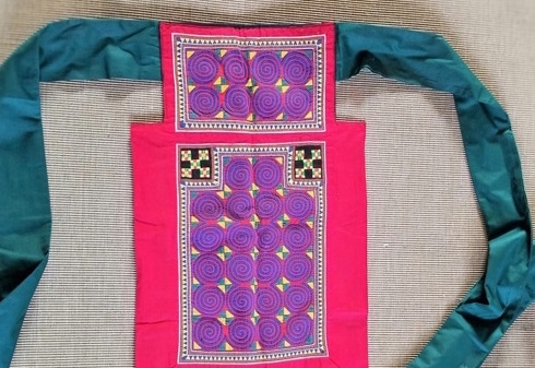 an image of a Hmong baby carrier with embroidery and teal straps