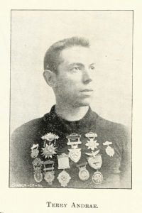 a young man with many bike racing medals pinned to his chest