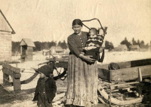 an Ojibwe woman holding a baby in a cradleboard