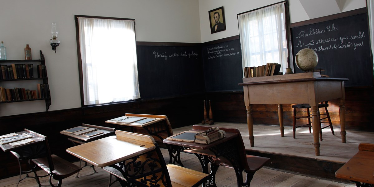The interior of a one room school house showing exercises on the blackboard