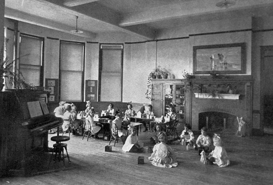Image of several children sitting before a fireplace playing with toys