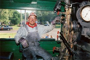 Color photograph of an engineer inside Soo Line 1003's engine