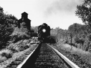 a black and white photo of an engine on the tracks and a conductor waving from the window