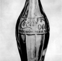 black and white image of an old soda bottle