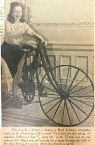 a young woman sits on the wooden bike and smiles at the camera.