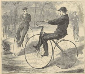 three men ride velocipedes, bicycles with a front wheel that is larger than the back wheel.