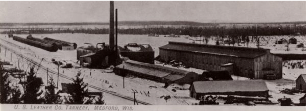 A black and white photo of a long low building with a tall smoke stack